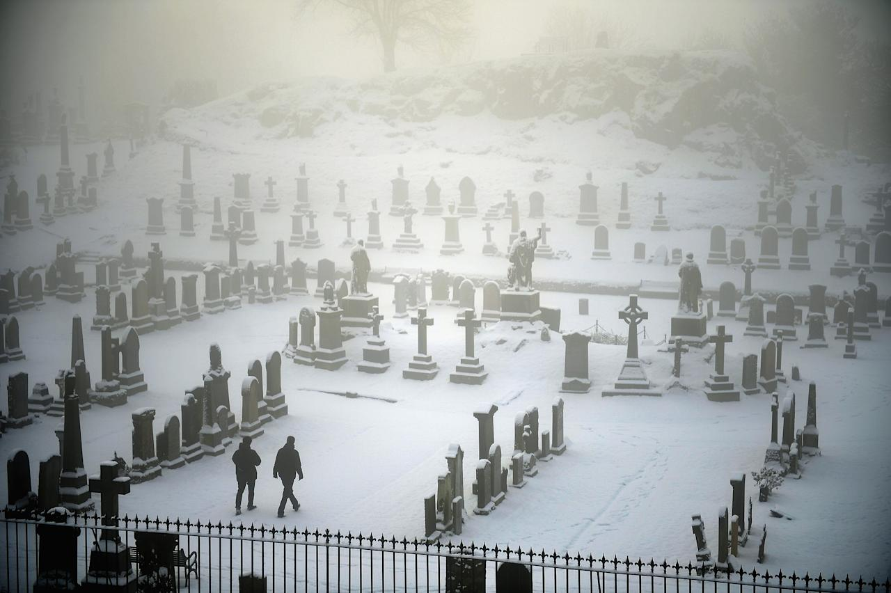STIRLING, UNITED KINGDOM - DECEMBER 03:  Two men walk through Stirling Castle graveyard on December 3, 2012 in Stirling, Scotland. Snow and sleet has hit many parts of Scotland with heavier falls expected over higher grounds.  (Photo by Jeff J Mitchell/Getty Images)
