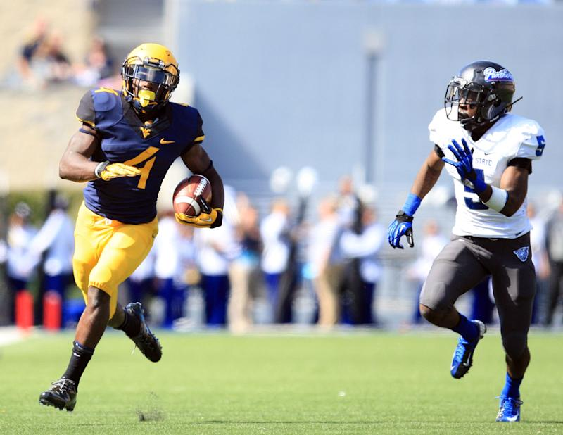 West Virginia running back Wendell Smallwood (4)  carries the ball toward the end zone as Georgia State's  Demarius Matthews (5) chases during the fourth quarter of an NCAA college football game in Morgantown, W.Va., on Saturday, Sept. 14, 2013. West Virginia won 41-7