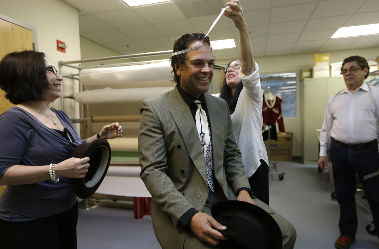 """Former MLB baseball player Mike Piazza is fitted for his costume by Maria Morales for his role in """"Slaughter on Tenth Avenue"""" at the Miami City Ballet, as costume designer Haydee Morales, looks on at left, Tuesday, April 16, 2013, in Miami Beach, Fla. Piazza will play a gangster in the ballet on May 3. He will say a few lines and then watch the rest of the performance from a seat onstage. Piazza says his turn with the troupe is his gift to his 6-year-old daughter, a student at Miami City Ballet School. (AP Photo/Lynne Sladky)"""