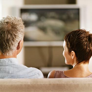 Rear-view-of-a-mature-couple-sitting-side-by-side-on-sofa_web