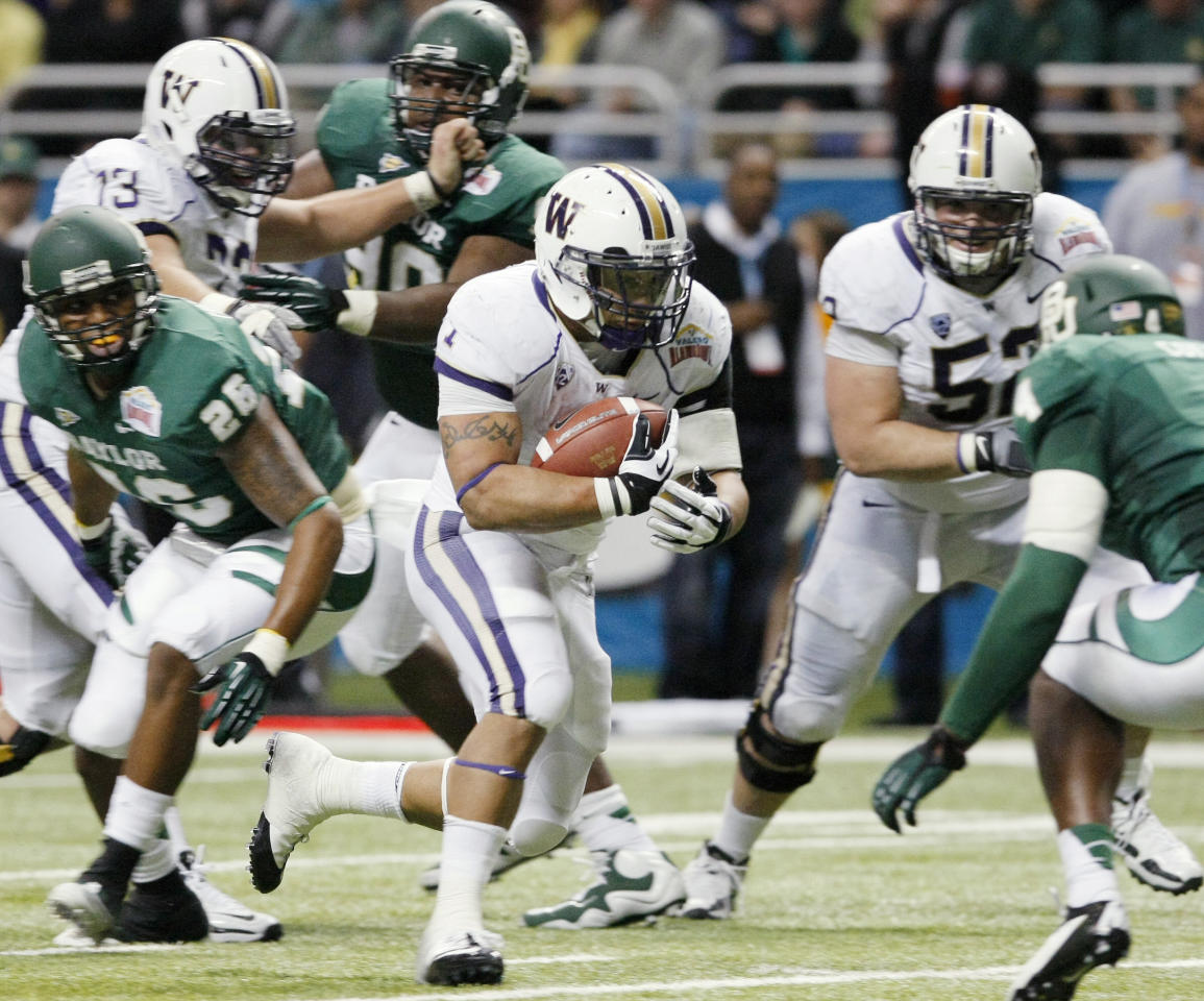 Washington's Chris Polk, center, rushes during the first half of the Alamo Bowl college football game against Baylor, Thursday, Dec. 29, 2011, at the Alamodome in San Antonio. (AP Photo/Darren Abate)
