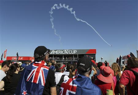 Emirates Team New Zealand fans watch as Team Oracle aerobatic pilot Sean Tucker performs prior to Race 1 of the 34th America's Cup yacht sailing race in San Francisco