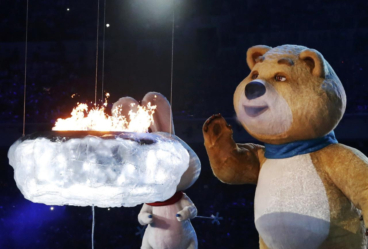 The Olympic Games mascots extinguish the Olympic flame in a small cauldron in the stadium during the closing ceremony for the Sochi 2014 Winter Olympics, February 23, 2014. REUTERS/Lucy Nicholson (RUSSIA - Tags: SPORT OLYMPICS)