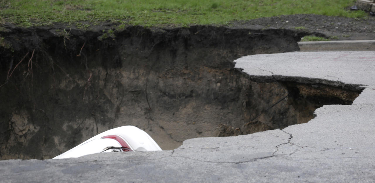 A section of a car can be seen in a gaping sinkhole that opened up a residential street on Chicago's South Side after a cast iron water main dating back to 1915 broke during a massive rain storm Thursday, April 18, 2013, in Chicago. The hole spanned the entire width of the road and chewed up grassy areas abutting the sidewalk. Two of the cars that disappeared inside had been parked, but a third was being driven when the road buckled and caved in. Only the hood of one of the vehicles could be seen peeking from the chasm.(AP Photo/M. Spencer Green)