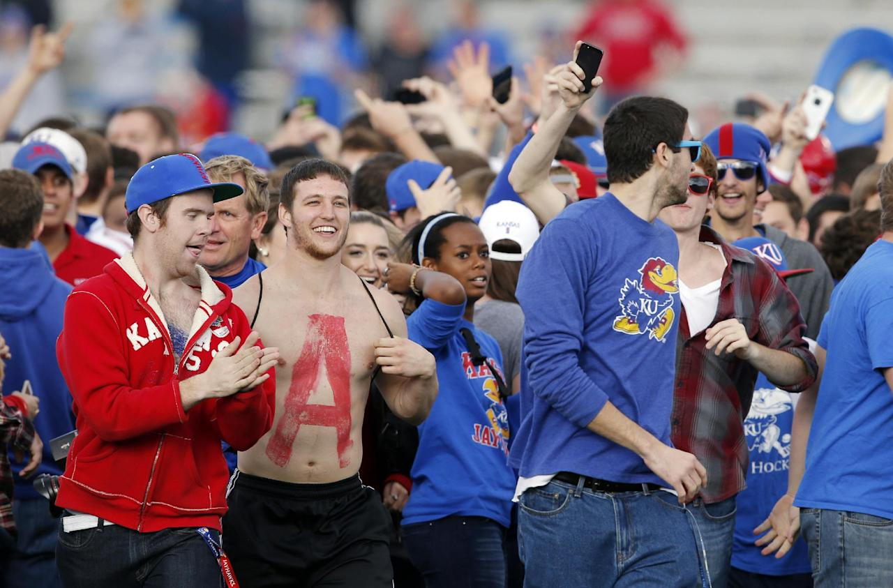 Kansas fans run onto the field after their 31-19 win over West Virginia in an NCAA college football game at Kansas Memorial Stadium in Lawrence, Kan., Saturday, Nov. 16, 2013. (AP Photo/Orlin Wagner)