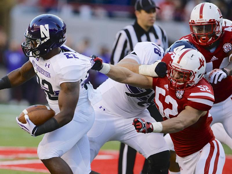 In this Nov. 2, 2013, photo, Nebraska linebacker Josh Banderas (52) grabs the jersey of Northwestern running back Treyvon Green (22) during an NCAA college football game in Lincoln, Neb. Banderas and a member of the men's track team face felony charges in connection with the thefts of seven bicycles on campus. Sgt. Douglas Petersen said Tuesday, May 13, 2014, that university police received a report of two individuals using bolt cutters to remove bikes from racks and loading the bikes into a pickup about 5 p.m. Monday. Lincoln police stopped the pickup near campus and arrested Banderas and Lucas Keifer