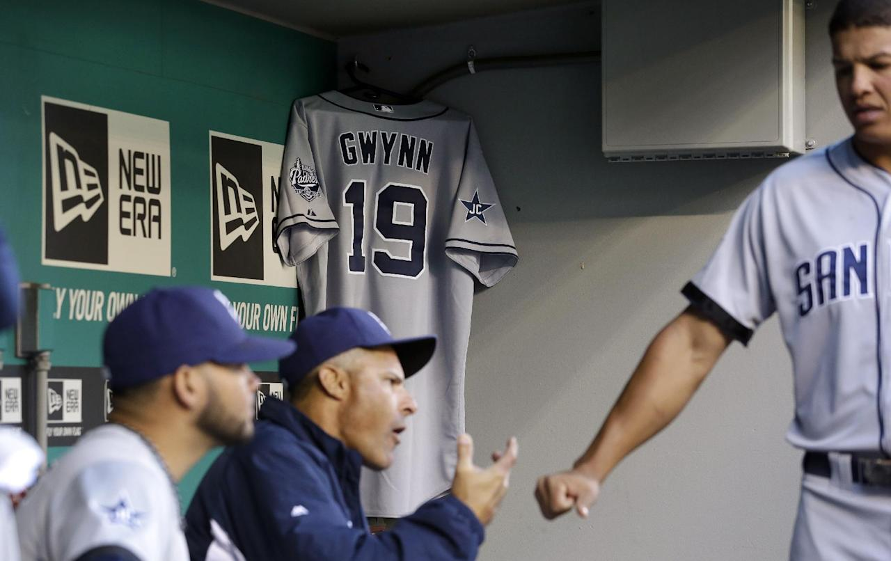 San Diego Padres' Will Venable, right, greets coach Jose Valentine near a jersey hanging in the team's dugout honoring Tony Gwynn before a baseball game against the Seattle Mariners Monday, June 16, 2014, in Seattle. It was announced earlier Monday that Gwynn, who had more than 3,100 hits during a career spanning two decades, died at age 54 following a battle with oral cancer. (AP Photo/Elaine Thompson)
