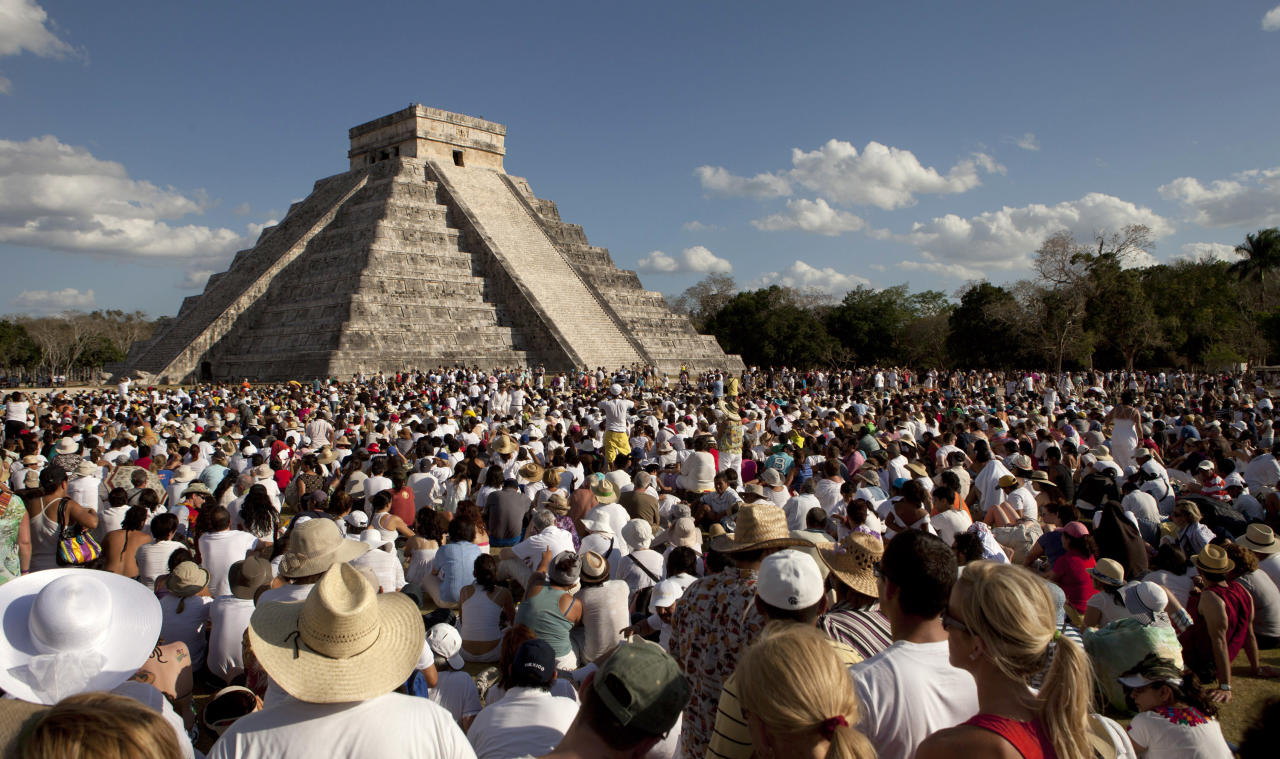 People look at the pyramid of Chichen Itza in the southern Mexican state of Yucatan March 21, 2012. Hundreds of Mexicans and tourists gathered at Chichen Itza to welcome spring at the Mayan pyramid El Castillo (The Castle), a temple to Kukulkan, the feathered serpent and Mayan snake deity. REUTERS/Victor Ruiz Garcia (MEXICO - Tags: SOCIETY)