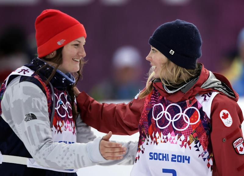 Canada's Dara Howell, right, celebrates with silver medalist  Devin Logan of the United States after Howell took the gold medal in the women's freestyle skiing slopestyle final at the Rosa Khutor Extreme Park at the 2014 Winter Olympics, Tuesday, Feb. 11, 2014, in Krasnaya Polyana, Russia