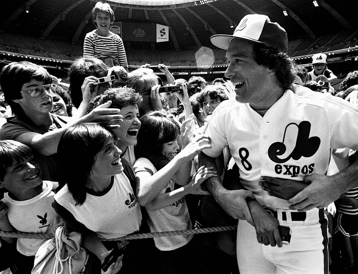FILE - In this June 24, 1983 file photo, Montreal Expos catcher Gary Carter is mobbed by admiring fans at camera day prior to a baseball game against the Pittsburgh Pirates in Montreal. Baseball Hall of Fame president Jeff Idelson said Thursday, Feb. 16, 2012, that Hall of Fame catcher Gary Carter has died. (AP Photo/The Canadian Press, Bernard Brault, File)