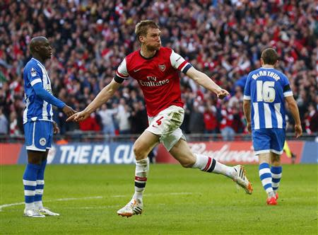 Arsenal's Per Mertesacker celebrates his goal against Wigan Athletic during their English FA Cup semi-final soccer match at Wembley Stadium in London