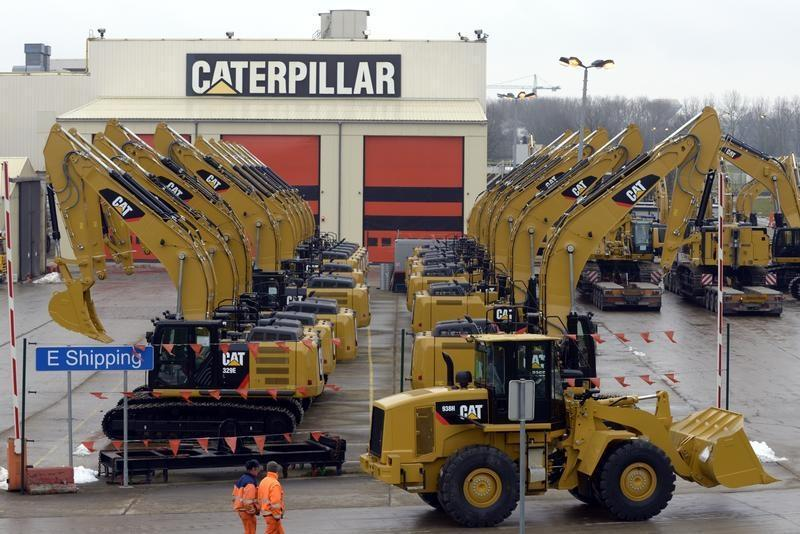Workers walk past Caterpillar excavator machines at a factory in Gosselies