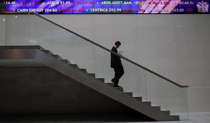 A man walks down steps under a share price ticker at the London Stock Exchange in the City of London