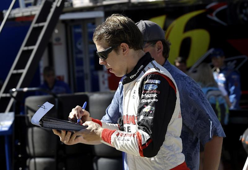 Brad Keselowski signs an autograph prior to practice for Sunday's NASCAR Sprint Cup series Coca-Cola 600 auto race at the Charlotte Motor Speedway in Concord, N.C., Saturday, May 24, 2014