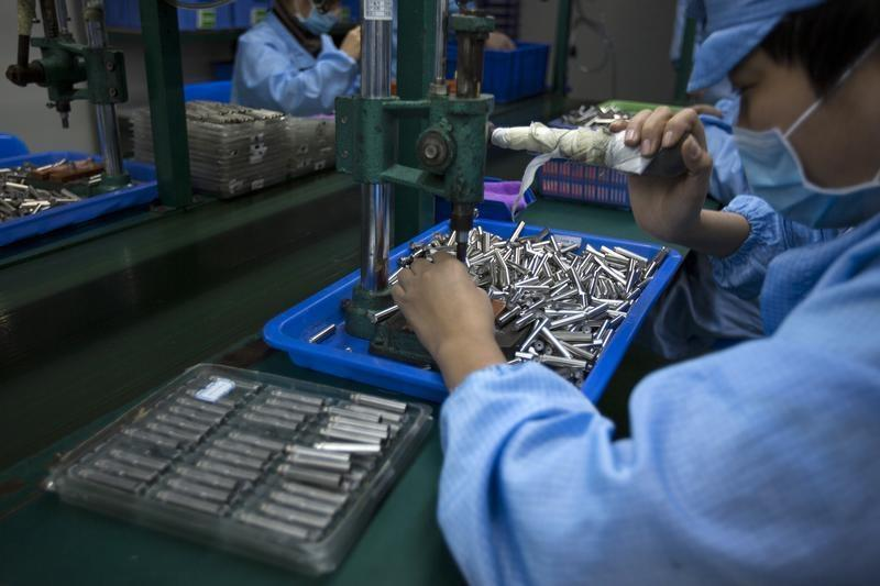 Employees work on electronic cigarettes at a production line in a factory in Shenzhen, southern Chinese province of Guangdong