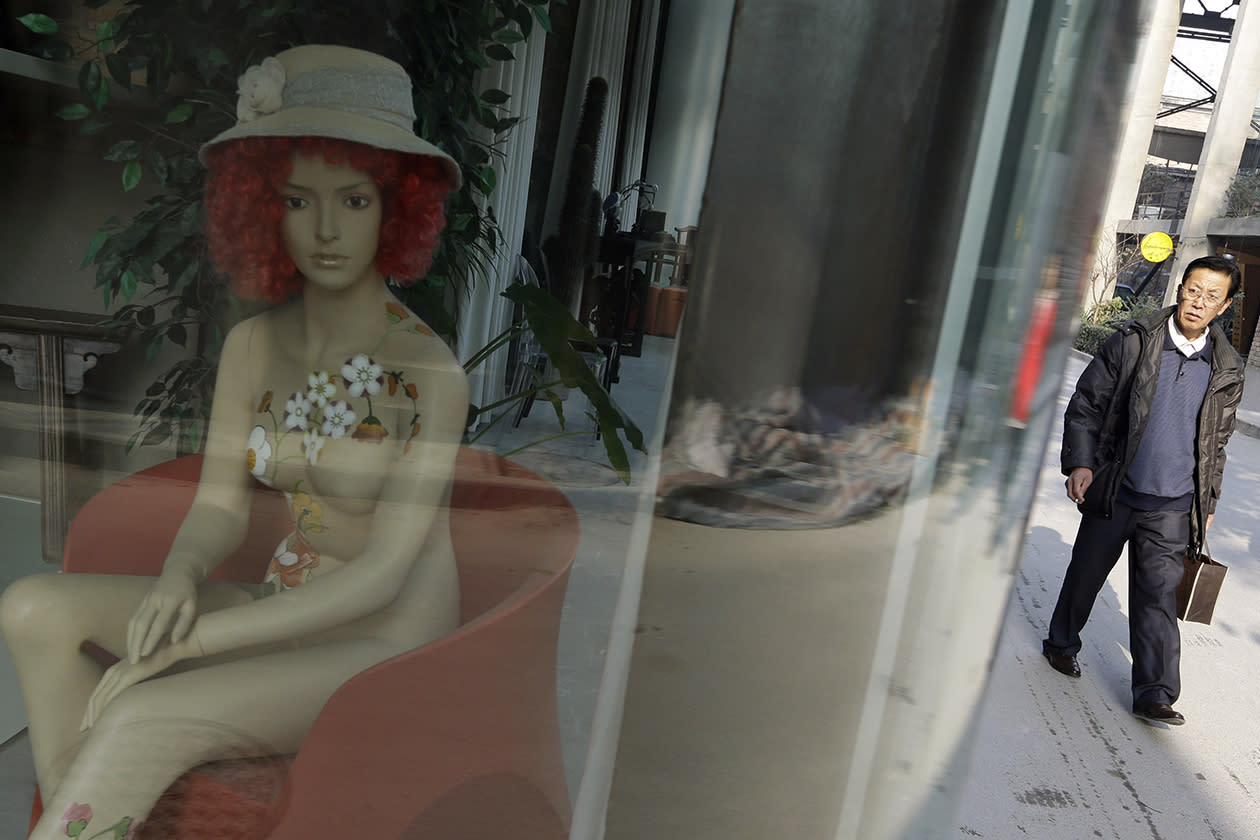 A man passes by a mannequin, displayed inside a cafe at the 798 Art District.