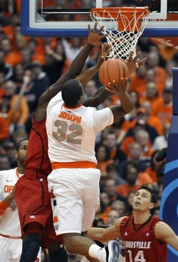 Syracuse's Kris Joseph (32) shoots against Louisville's Gorgui Dieng during the first half of an NCAA college basketball game in Syracuse, N.Y., Saturday, March 3, 2012. (AP Photo/KevinRivoli)