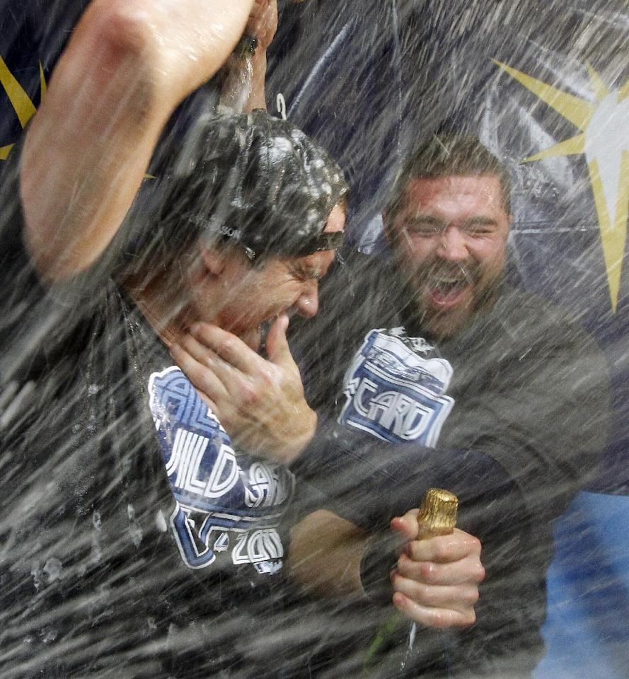 Tampa Bay Rays' Evan Longoria, left, and Kelly Shoppach celebrate with champagne early Thursday, Sept. 29, 2011, after the Rays defeated the New York Yankees 8-7 in a baseball game and clinched the AL wild card in St. Petersburg, Fla. (AP Photo/Mike Carlson)