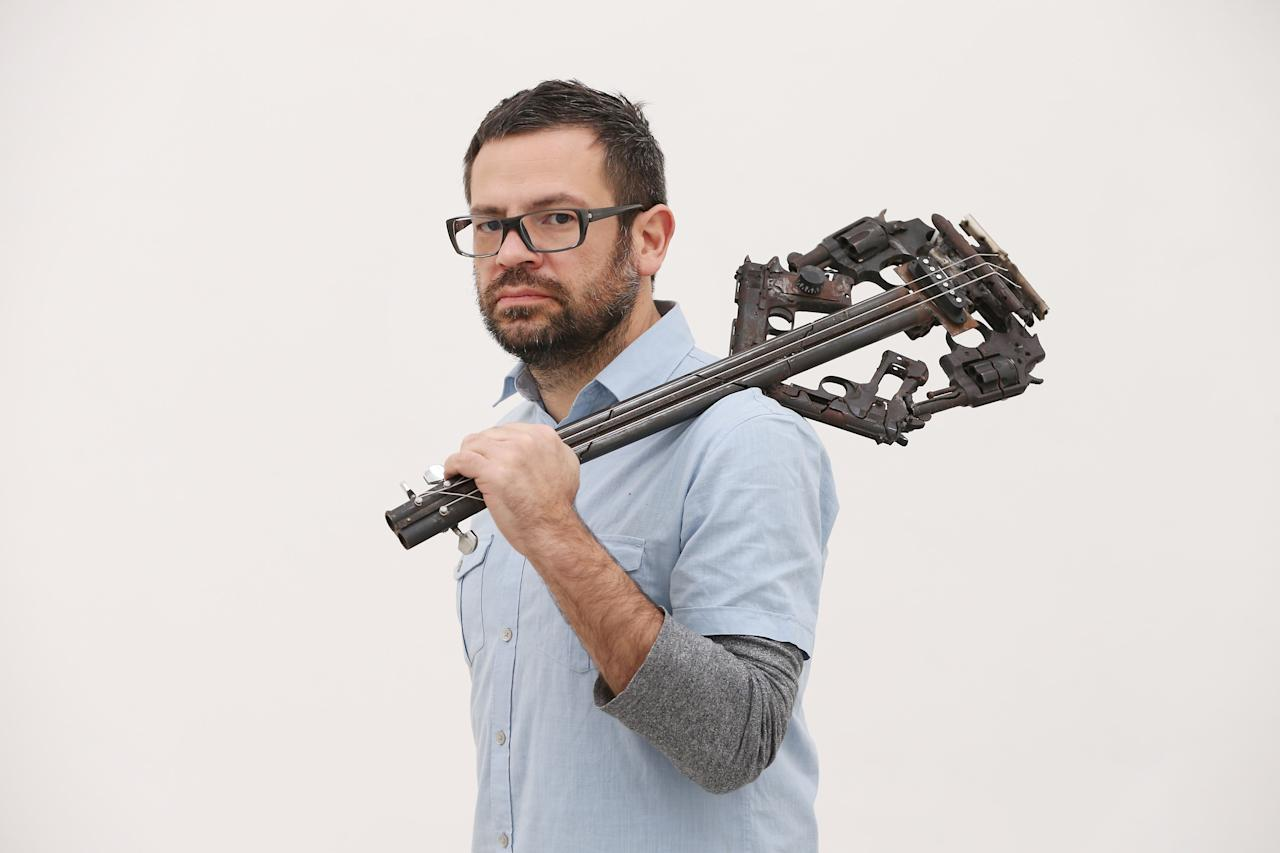 LONDON, ENGLAND - MARCH 26:  Artist Pedro Reyes holds one of his musical instruments sculpted from recycled guns at the Lisson Gallery on March 26, 2013 in London, England.  Mexican artist Pedro Reyes received 6,700 destroyed weapons from the Mexican government from which he sculpted two groups of instruments. The first, a series titled Imagine, is an orchestra of fifty instruments, from flutes to string and percussion instruments, designed to be played live. The second, Disarm, is an installation of mechanical musical instruments, which can either be automated or played live by an individual operator using a laptop computer or midi keyboard.  (Photo by Peter Macdiarmid/Getty Images)
