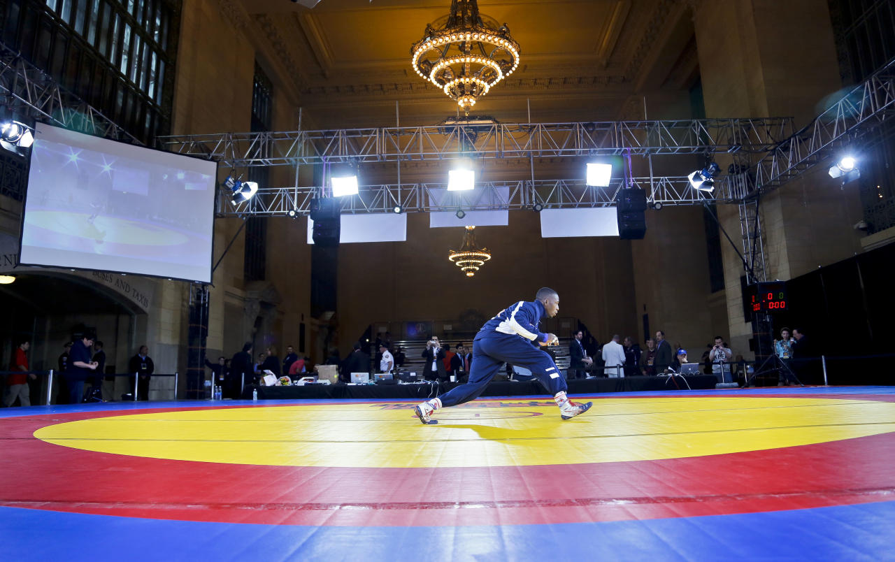 "U.S. freestyle wrestler Obe Blanc warms up for an exhibition wrestling match at Grand Central Terminal, Wednesday, May 15, 2013, in New York. ""The Rumble on the Rails"" exhibition, featuring teams from the USA, Iran and Russia, raises money for charity but is also aimed at drawing attention to the sport's attempt to stay in the Olympics. (AP Photo/Bebeto Matthews)"