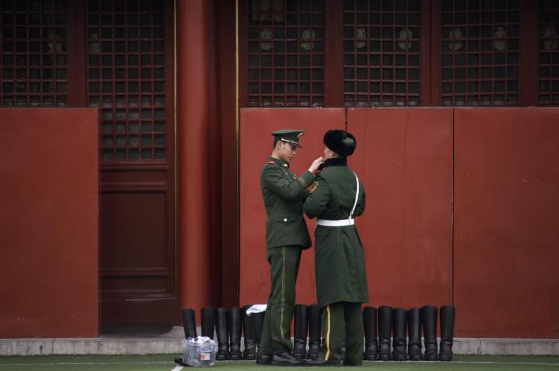 A paramilitary police officer adjusts his colleague's uniform during the week-long Chinese New Year holiday at the Forbidden City compound in Beijing