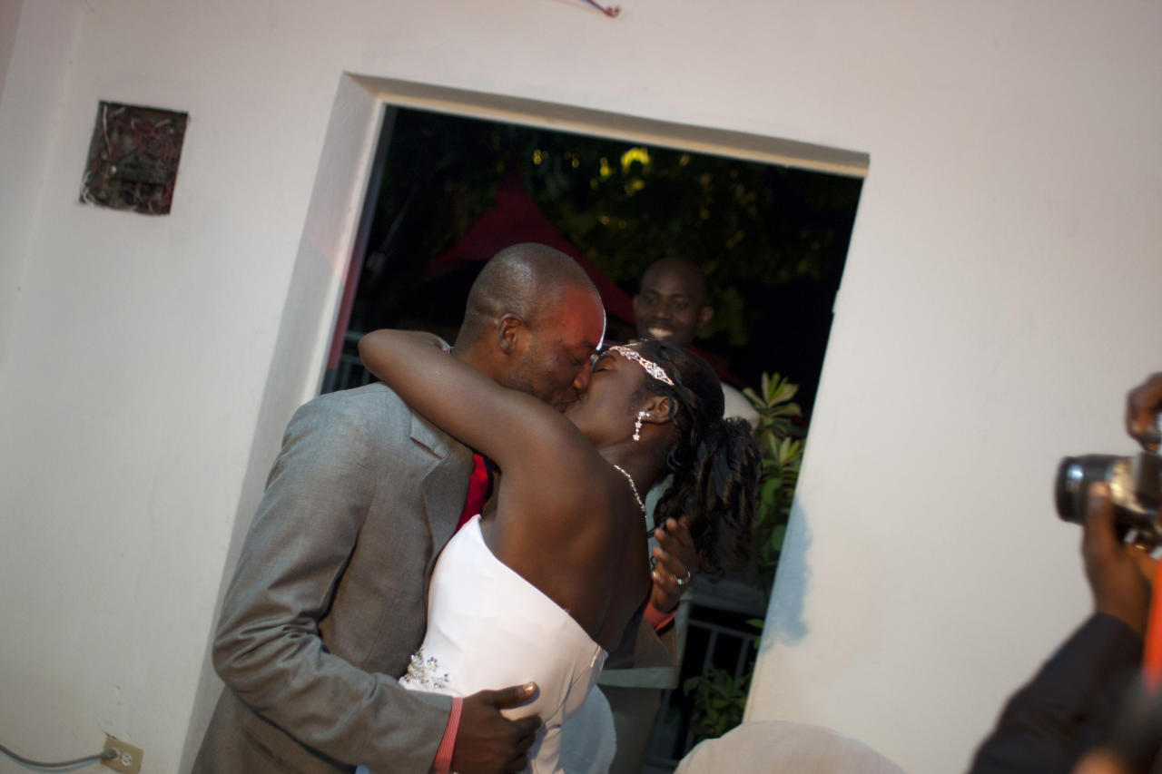 In this July 20, 2012 photo, professional dancer Georges Exantus kisses his wife Sherly Henrisme Exantus on their wedding night in Port-au-Prince, Haiti. The earthquake three years ago in Haiti's capital flattened the apartment where Georges Exantus was living and he spent three days trapped under a heap of jagged rubble. After friends dug him out, doctors amputated his right leg just below the knee. Three years later, the 32-year-old professional dancer is back on the floor, spinning away as he does the salsa, cha-cha and samba. A prosthetic leg doesn't hold him back. (AP Photo/Dieu Nalio Chery)