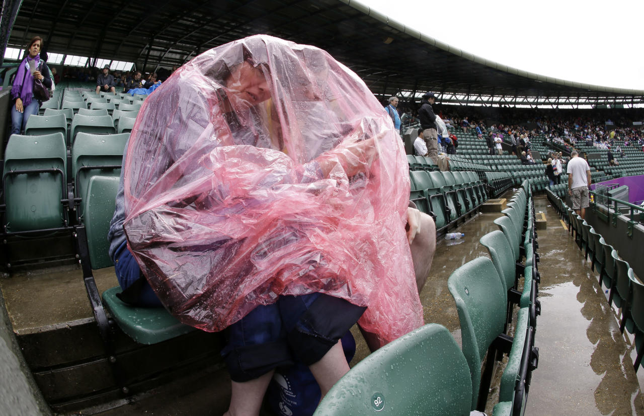 Donna Marshall and David Thorpe wait for the rain to stop at the All England Lawn Tennis Club at Wimbledon, in London, at the 2012 Summer Olympics, Sunday, July 29, 2012. (AP Photo/Mark Humphrey)