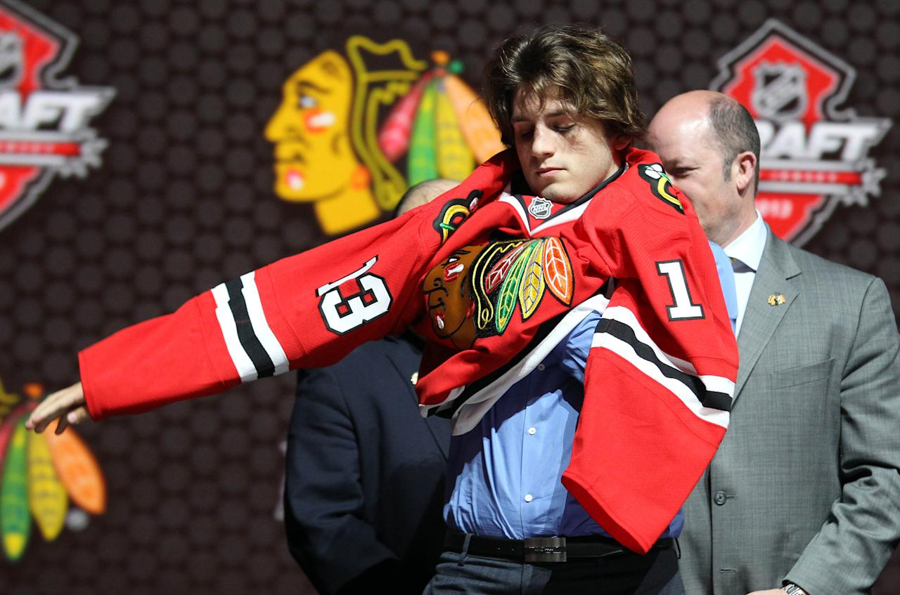 Jun 30, 2013; Newark, NJ, USA; Ryan Hartman puts on a jersey after being introduced as the number thirty overall pick to the Chicago Blackhawks during the 2013 NHL Draft at the Prudential Center. (Ed Mulholland-USA TODAY Sports)