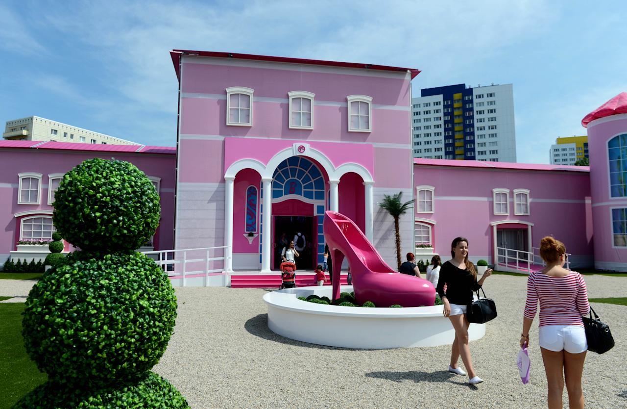 Visitors stand in front of the Barbie Dreamhouse Experience near Alexanderplatz square in Berlin, Germany, Thursday May 16, 2013. The 2,500 square meter Barbie Dreamhouse Experience will be open for three months in Berlin. (AP Photo/dpa, Jens Kalaene)
