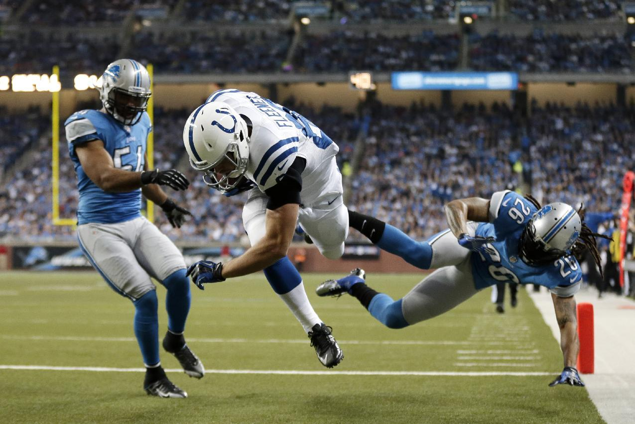 Indianapolis Colts tight end Coby Fleener (80), defended by Detroit Lions free safety Louis Delmas (26) and linebacker DeAndre Levy (54), falls into the end zone for a touchdown during the second quarter of an NFL football game at Ford Field in Detroit, Sunday, Dec. 2, 2012. (AP Photo/Paul Sancya)