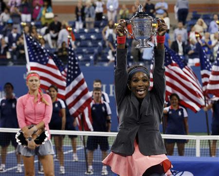 Serena Williams of the U.S. raises her trophy after defeating Victoria Azarenka of Belarus (L, holding runner up trophy) in their women's singles final match at the U.S. Open tennis championships in New York September 8, 2013. REUTERS/Mike Segar