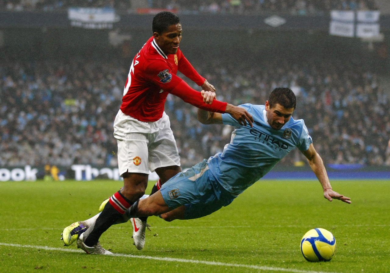 Manchester City's Aleksandar Kolarov, right, vies for the ball against Manchester United's Antonio Valencia during their FA Cup third round soccer match at Etihad Stadium, Manchester, England, Sunday, Jan. 8, 2012. (AP Photo/Tim Hales)