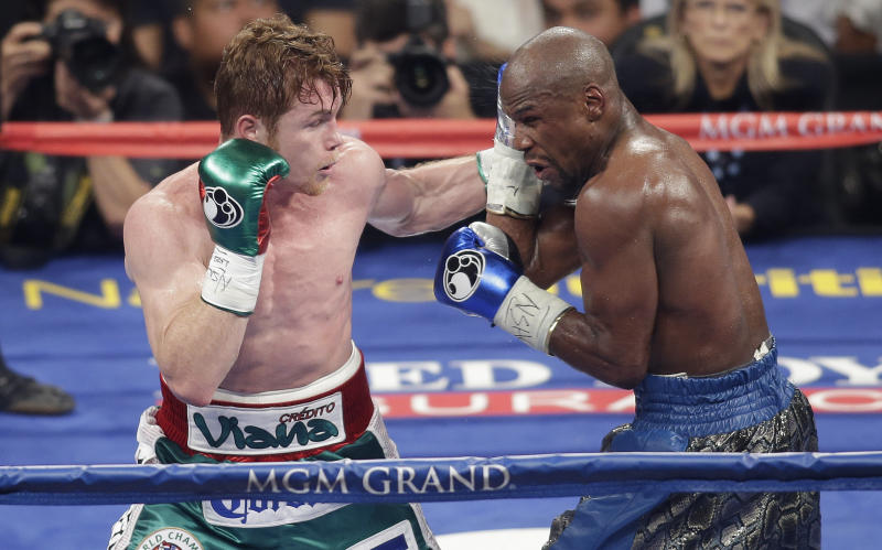 Canelo Alvarez, left, throws a punch against Floyd Mayweather Jr. during their fight last year in Las Vegas. (Isaac Brekken/Associated Press)