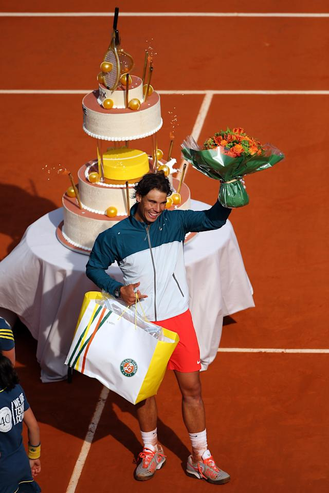 PARIS, FRANCE - JUNE 03:  Rafael Nadal of Spain waves to the crowd after being presented with a birthday cake after victory in his Men's Singles match against Kei Nishikori of Japan during day nine of the French Open at Roland Garros on June 3, 2013 in Paris, France.  (Photo by Julian Finney/Getty Images)