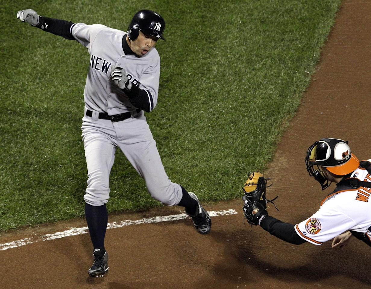 New York Yankees' Ichiro Suzuki, left, of Japan, runs past Baltimore Orioles catcher Matt Wieters to score a run on a double by Robinson Cano in the first inning of Game 2 of the American League division baseball series on Monday, Oct. 8, 2012, in Baltimore. (AP Photo/Patrick Semansky)