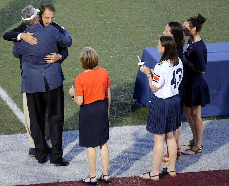 Auburn University head football coach Gus Malzahn, facing, hugs Philip Lutzenkirchen's father during a memorial service Wednesday, July 2, 2014 at Lassiter High School in East Cobb, Ga. Several hundred mourners attended Philip Lutzenkirchen's public memorial service and candlelight vigil Wednesday night, nearly filling the bleachers on one side of his old high school stadium less than four days after the popular former Auburn player's death