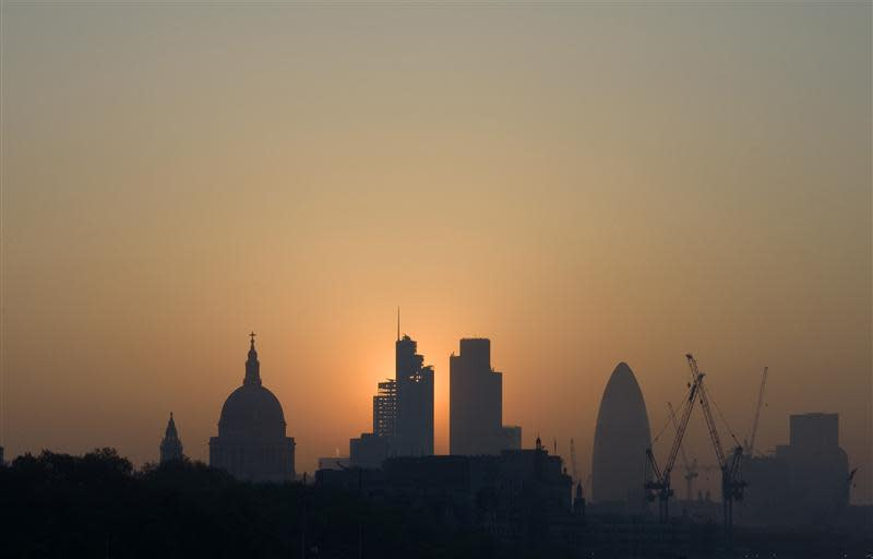 File photo of the sun rising above the financial district of the City of London