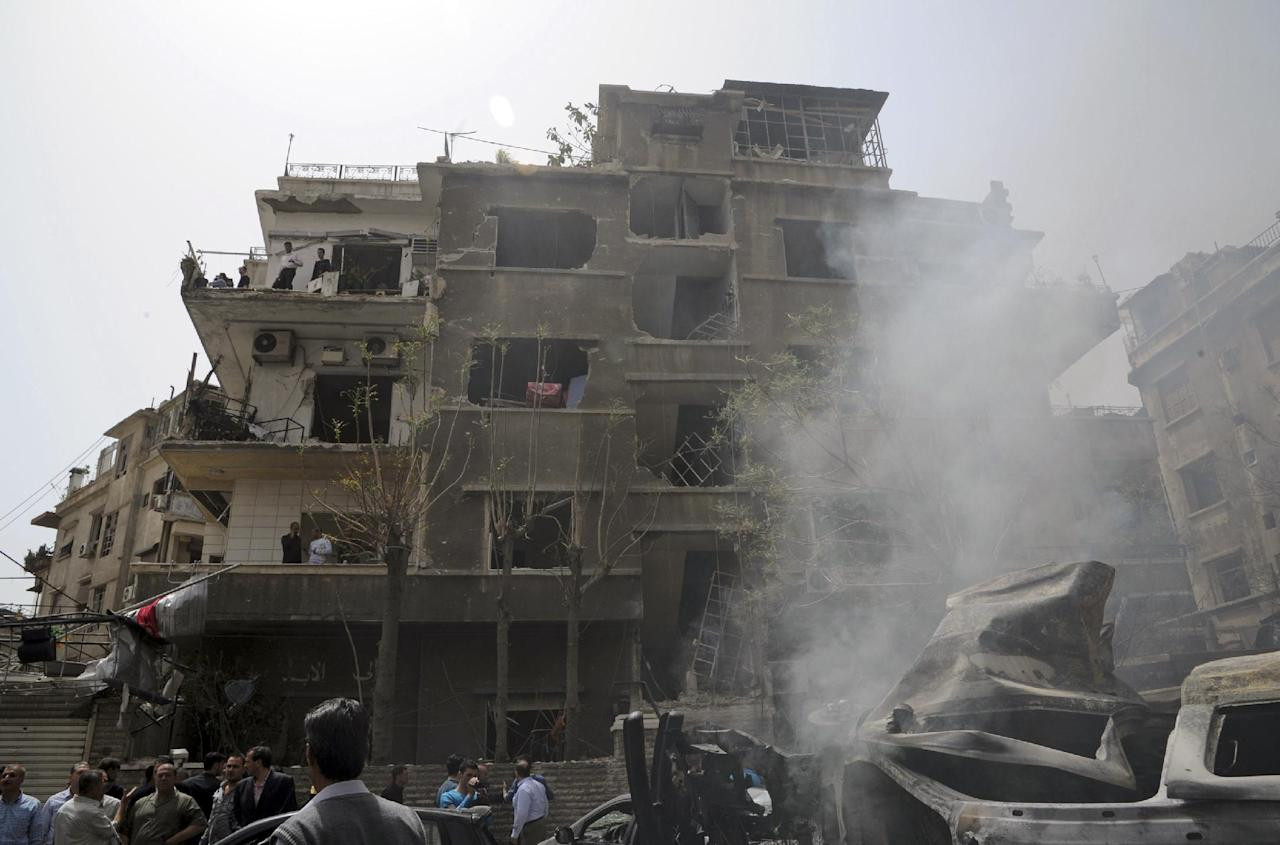 This photo released by the Syrian official news agency SANA, shows Syrians gathering beneath the shattered facade of a building damaged by a car bomb, in Damascus, Syria, Monday, April. 8, 2013. A car bomb rocked a busy residential and commercial district in central Damascus on Monday, killing more than a dozen with many more injured and sending a huge cloud of black smoke billowing over the capital's skyline, Syrian state-run media said. (AP Photo/SANA)
