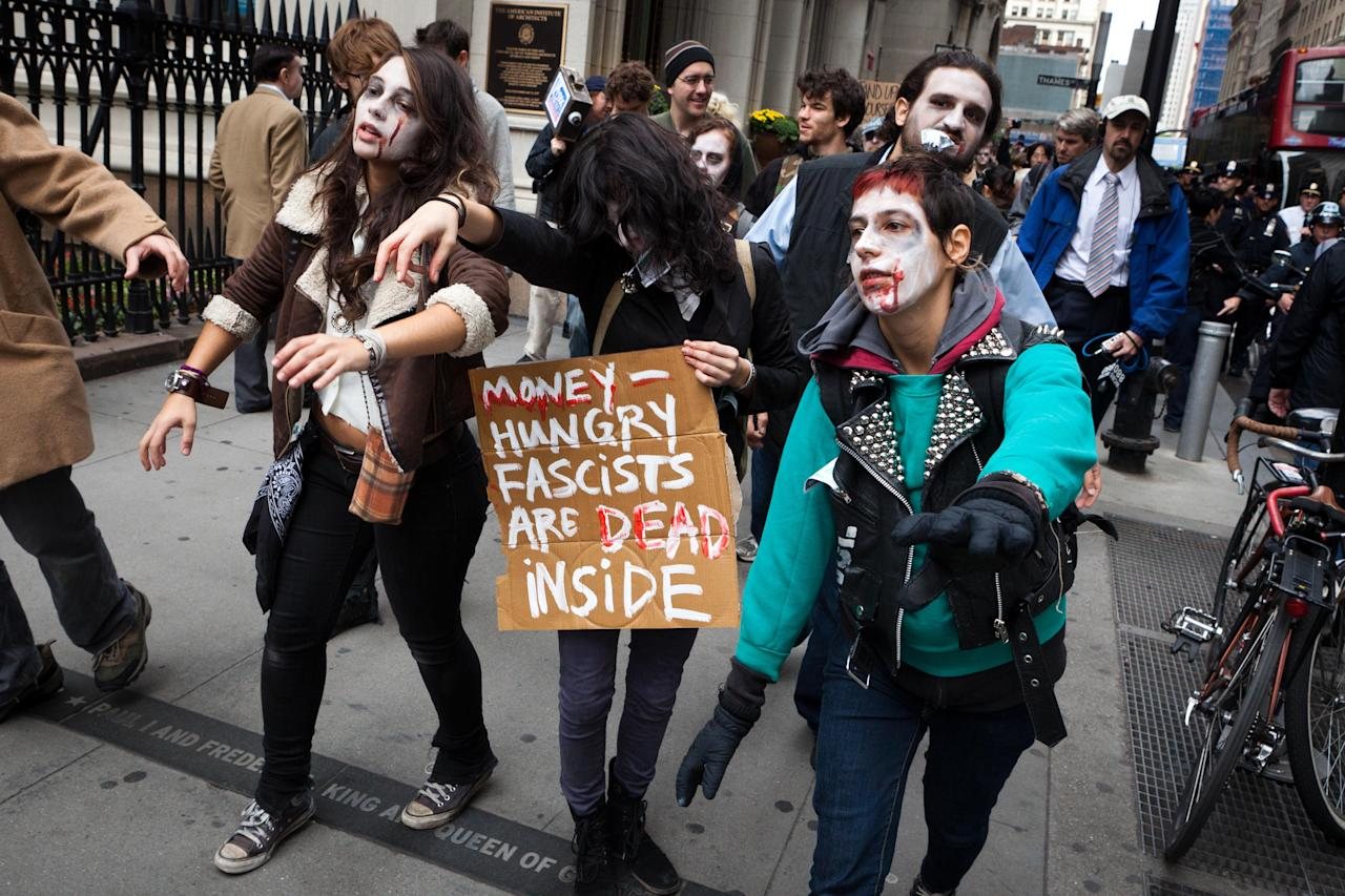 <p>               Protesters from Occupy Wall Street march through the financial district dressed as corporate zombies Monday, Oct. 3, 2011, in New York. The protests have gathered momentum and gained participants in recent days as news of mass arrests and a coordinated media campaign by the protestors have given rise to similar demonstrations around the country. (AP Photo/John Minchillo)