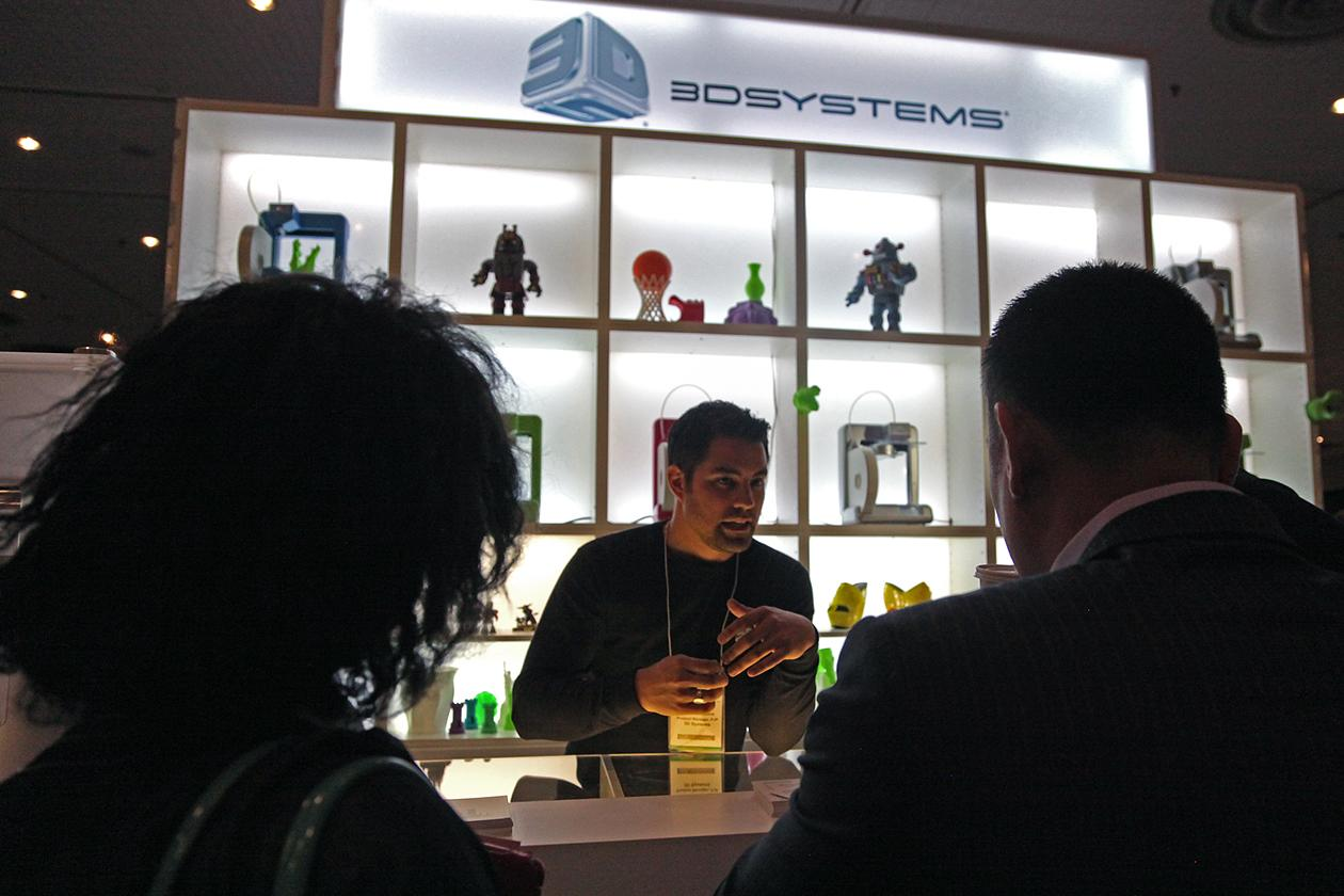 """Attendees gathered around <a target=""""_blank"""" href=""""http://www.cubify.com/"""">Cubify</a>'s booth, for a demonstration of the Cube 3D printer, a low cost printer marketed for home use."""