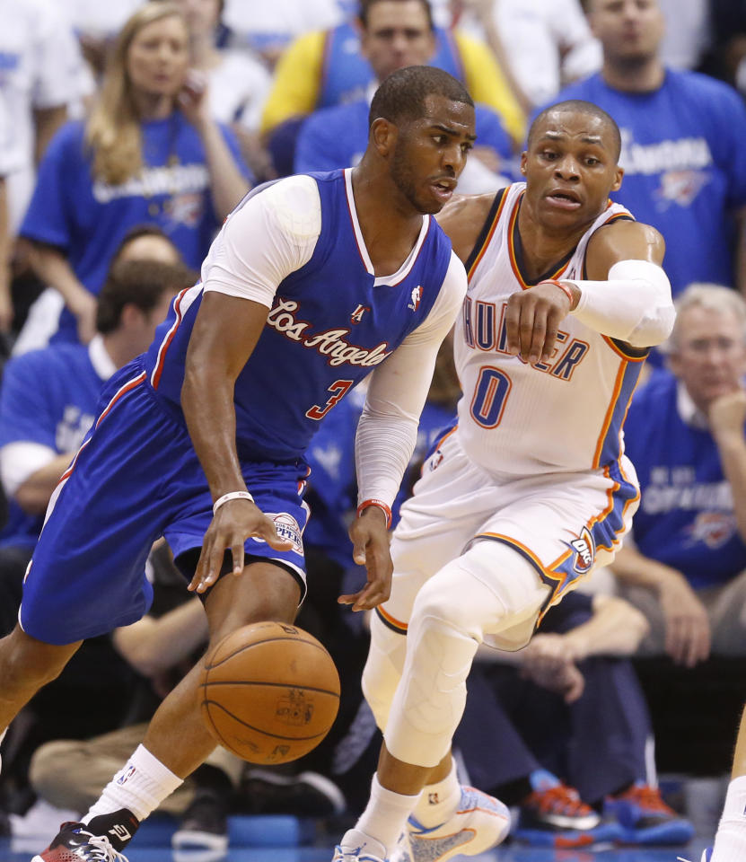Los Angeles Clippers guard Chris Paul (3) drives in front of Oklahoma City Thunder guard Russell Westbrook (0) in the third quarter of Game 2 of the Western Conference semifinal NBA basketball playoff series in Oklahoma City, Wednesday, May 7, 2014. Oklahoma City won 112-101. (AP Photo/Sue Ogrocki)
