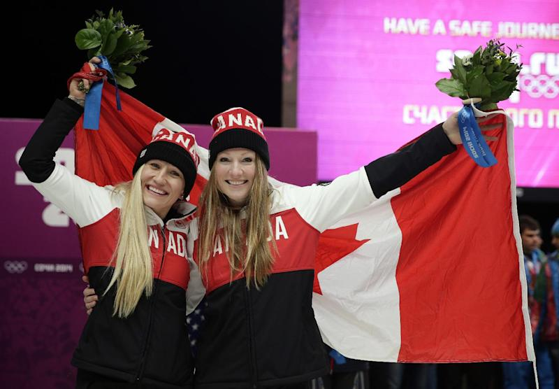 Gold medal winners from Canada Kaillie Humphries, left, and Heather Moyse hold the flag after the women's bobsled competition at the 2014 Winter Olympics, Wednesday, Feb. 19, 2014, in Krasnaya Polyana, Russia
