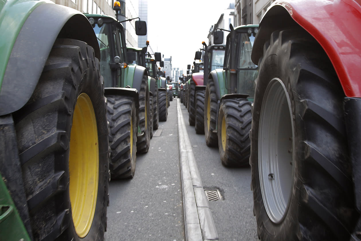European milk farmers drive their tractors down a main thoroughfare in the European quarter of Brussels.