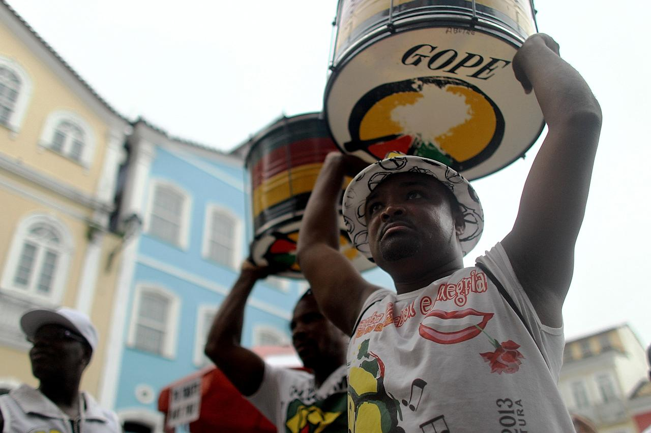 SALVADOR, BRAZIL - JANUARY 12: Olodum band members carry drums after performing in the street on January 12, 2014 in Salvador, Brazil. Salvador, the original capital of Brazil, will host six matches during the month-long 2014 FIFA World Cup which begins June 12. Salvador was the main port of entry in Brazil for African slave labor, receiving around 1.3 million Africans before slavery was abolished in Brazil. Salvador remains about 80 percent Afro-Brazilian today. (Photo by Mario Tama/Getty Images)