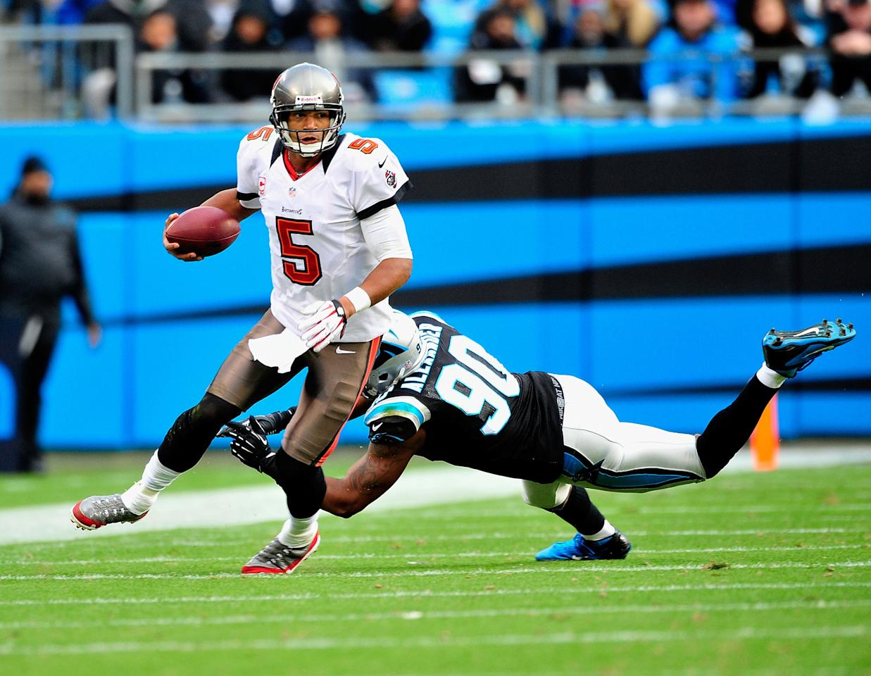 CHARLOTTE, NC - NOVEMBER 18:  Frank Alexander #90 of the Carolina Panthers misses the tackle as Josh Freeman #5 of the Tampa Bay Buccaneers scrambles out of the pocket during play at Bank of America Stadium on November 18, 2012 in Charlotte, North Carolina. Tampa Bay won 27-21 in overtime.  (Photo by Grant Halverson/Getty Images)