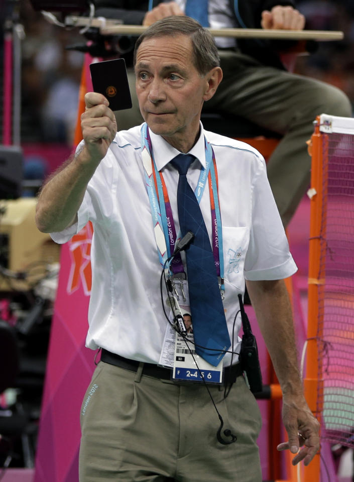 Head badminton referee Torsten Berg issues a black card to players in the women's doubles badminton match between Ha Jung-eun and Kim Min-jung, of South Korea, and Meiliana Jauhari and Greysia Polii, of Indonesia, at the 2012 Summer Olympics, Tuesday, July 31, 2012, in London. (AP Photo/Andres Leighton)