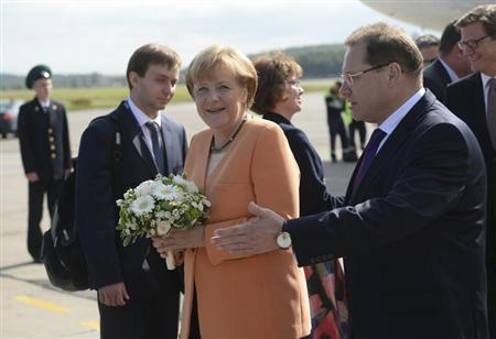 German Chancellor Angela Merkel receives flowers as she arrives to take part in the G20 Summit in St. Petersburg, September 5, 2013. REUTERS/Alexei Filippov/RIA Novosti/Pool