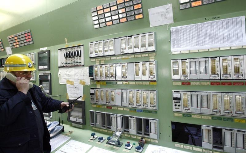 An employee of an oil control unit uses a phone to instruct workers at the oil refinery of Baiji