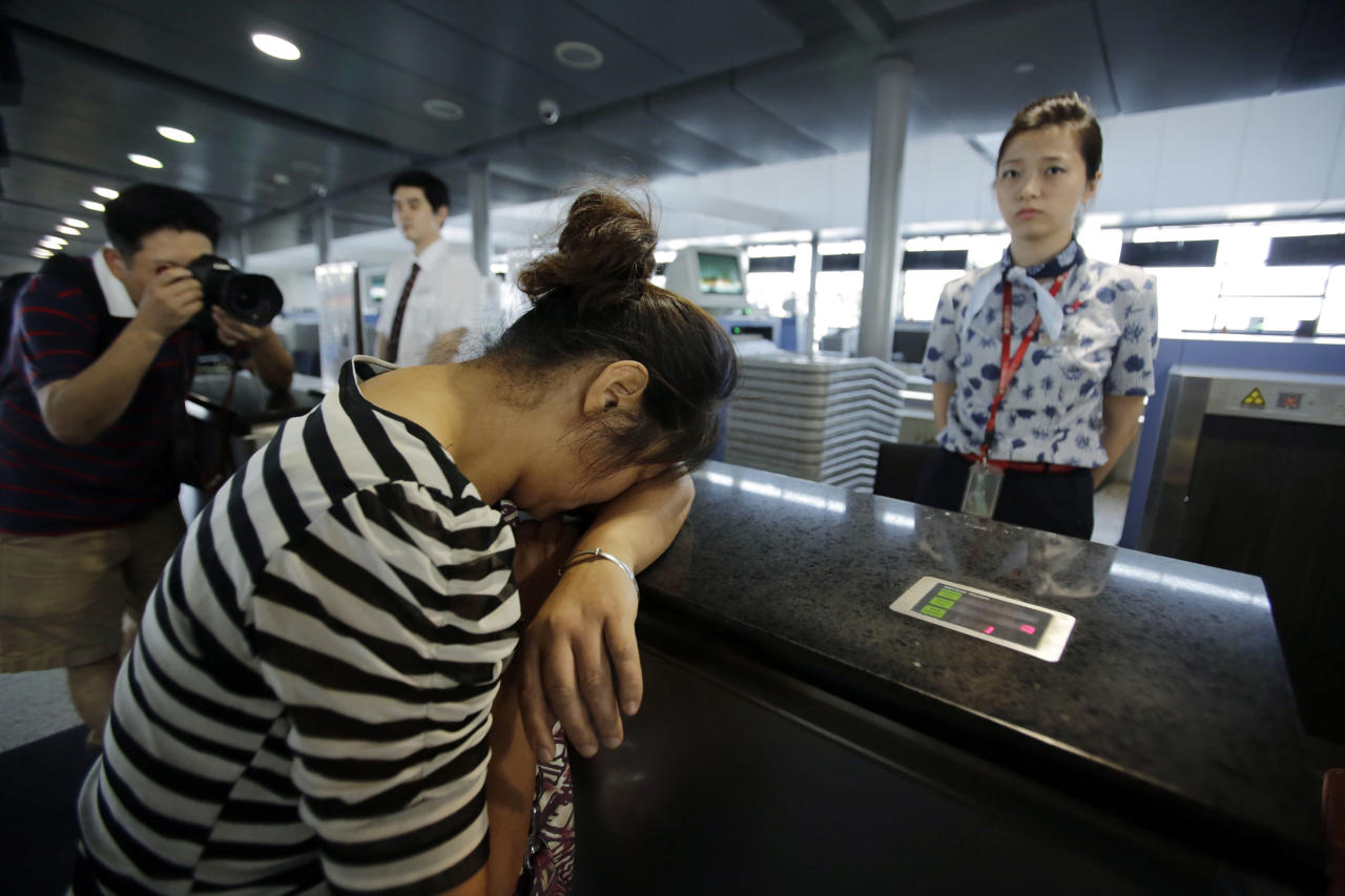 An unidentified family member of one of two Chinese students killed in a crash of Asiana Airlines' plane on Saturday, cries at the Airlines' counter as she and other family members check in a flight to San Francisco at Pudong International Airport in Shanghai, China, Monday, July 8, 2013. The Asiana flight crashed upon landing Saturday, July 6, at San Francisco International Airport, and the two of the 307 passengers aboard were killed. (AP Photo/Eugene Hoshiko)