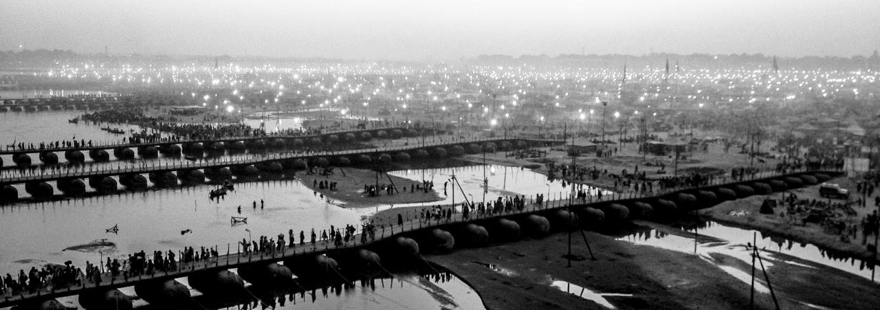 ALLAHABAD, INDIA - FEBRUARY 09: (EDITORS NOTE: Image was created using the iPhone panoramic application) Hindu pilgrims make their way over pontoon bridges near Sangam, the confluence of the holy rivers Ganges, Yamuna and the mythical Saraswati, during the Maha Kumbh Mela on February 9, 2013 in Allahabad, India. The Maha Kumbh Mela, believed to be the largest religious gathering on earth is held every 12 years on the banks of Sangam, the confluence of the holy rivers Ganga, Yamuna and the mythical Saraswati. The Kumbh Mela alternates between the cities of Nasik, Allahabad, Ujjain and Haridwar every three years. The Maha Kumbh Mela celebrated at the holy site of Sangam in Allahabad, is the largest and holiest, celebrated over 55 days, it is expected to attract over 100 million people. (Photo by Daniel Berehulak/Getty Images)